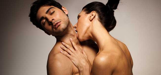 Una mujer besa a un hombre en el cuello para lo seducir y excitar